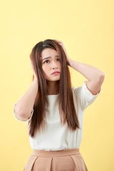 Giovane donna asiatica che ha uno stress isolato su sfondo giallo.
