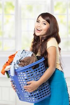 Giovane donna asiatica che giudica un canestro pieno di vestiti