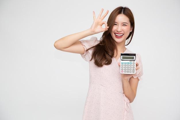 Calcolatrice della holding della giovane donna asiatica