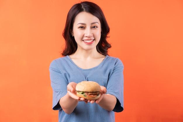 Giovane donna asiatica che tiene hamburger sull'arancia