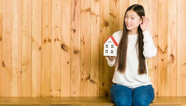 Giovane donna asiatica che tiene un'icona della casa che prova ad ascoltare un gossip.