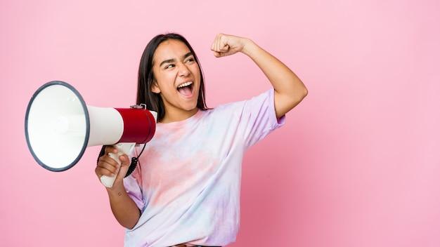 Giovane donna asiatica che tiene un megafono isolato sulla parete rosa che alza il pugno dopo una vittoria, concetto del vincitore