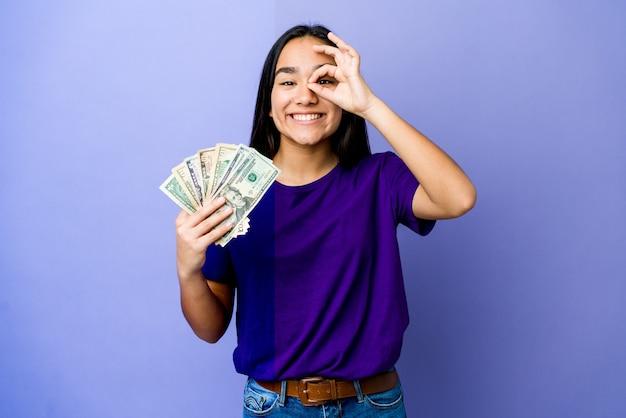 La giovane donna asiatica che tiene i soldi isolati sulla parete viola ha eccitato mantenendo il gesto giusto sull'occhio