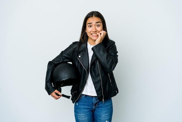 Giovane donna asiatica che tiene un casco della motocicletta sopra le unghie mordaci della parete isolata, nervosa e molto ansiosa.