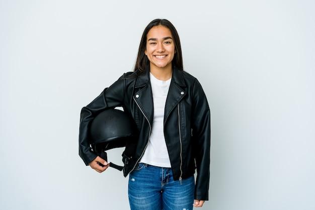 Giovane donna asiatica che tiene un casco della motocicletta sopra la parete isolata felice, sorridente e allegra.