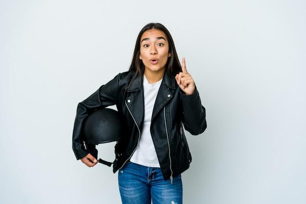 Giovane donna asiatica che tiene un casco della motocicletta sopra la parete isolata che ha un'idea