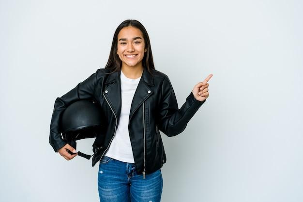 Giovane donna asiatica che tiene un casco della motocicletta sopra la parete isolata che sorride e che indica da parte, mostrando qualcosa nello spazio vuoto.