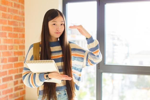 Giovane donna asiatica che tiene un oggetto con entrambe le mani sullo spazio laterale della copia, mostrando, offrendo o pubblicizzando un oggetto