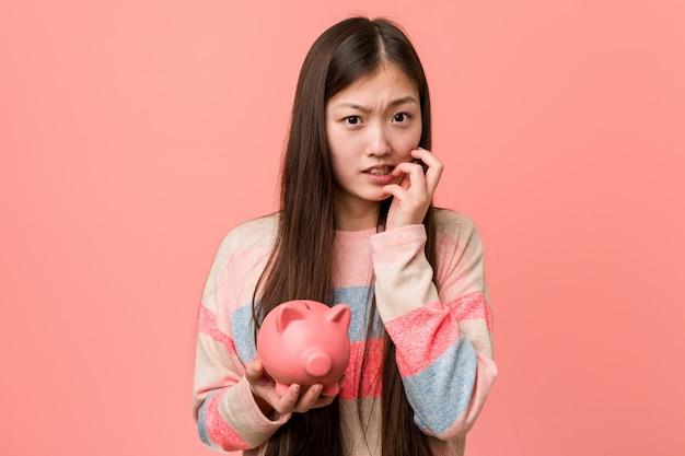Giovane donna asiatica che tiene le unghie mordaci di un porcellino salvadanaio, nervose e molto ansiose.