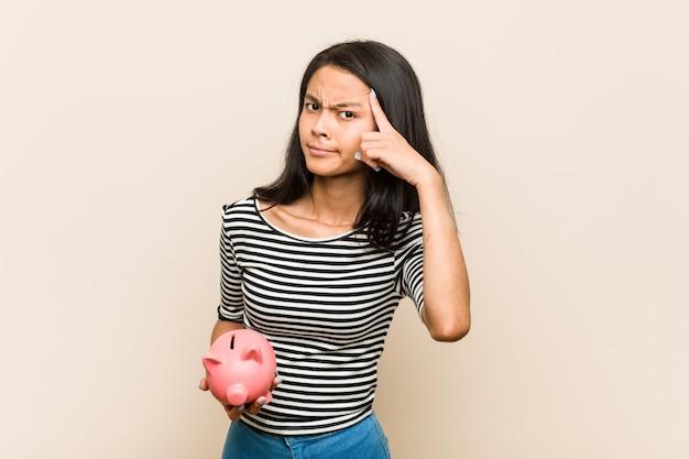Giovane donna asiatica che tiene un porcellino salvadanaio che mostra un gesto di delusione con l'indice.