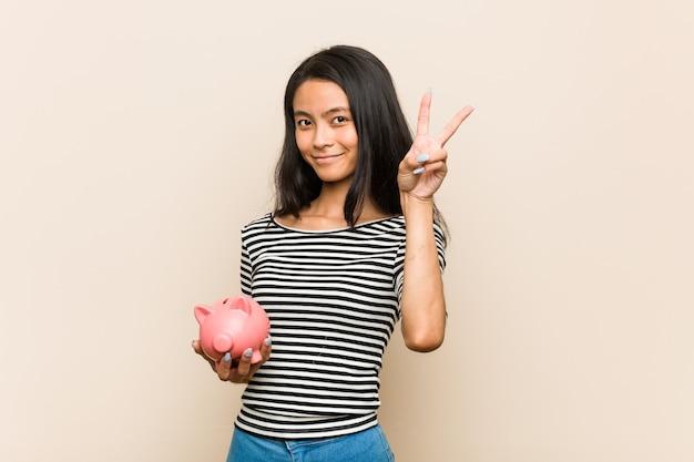 Giovane donna asiatica che tiene un salvadanaio che mostra il numero due con le dita.