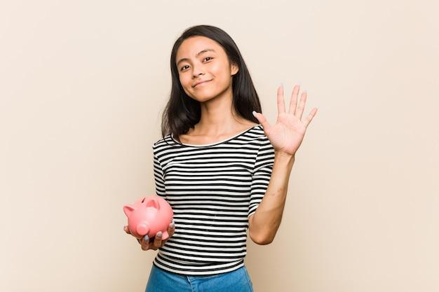 Giovane donna asiatica che tiene un salvadanaio