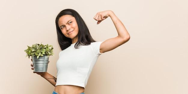 Giovane donna asiatica che tiene una pianta che alza il pugno dopo una vittoria, concetto del vincitore.