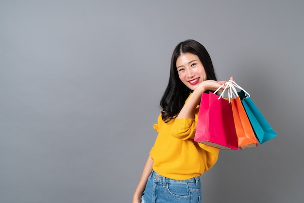 Giovane donna asiatica che tiene i sacchetti della spesa in camicia gialla su sfondo grigio