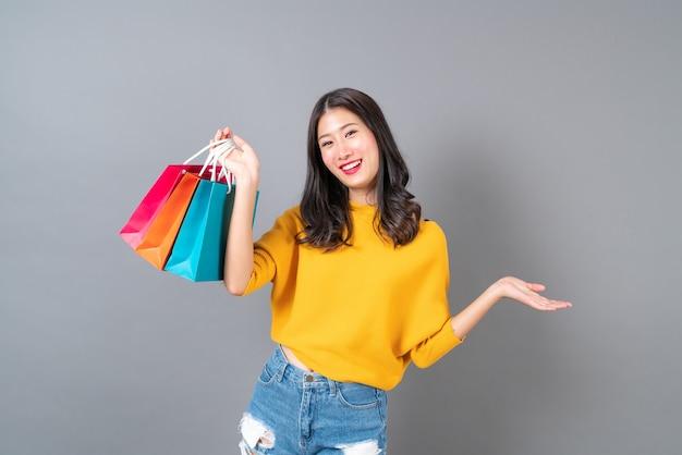 Giovane donna asiatica che tiene i sacchetti della spesa in camicia gialla su grigio