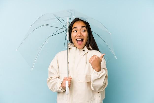 La giovane donna asiatica che tiene un ombrello punta con il dito pollice lontano, ridendo e spensierata.