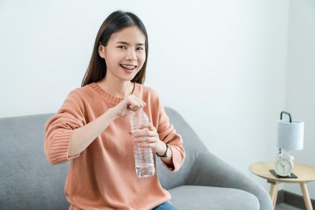 Giovane donna asiatica tenendo la bottiglia d'acqua e sul divano di casa.