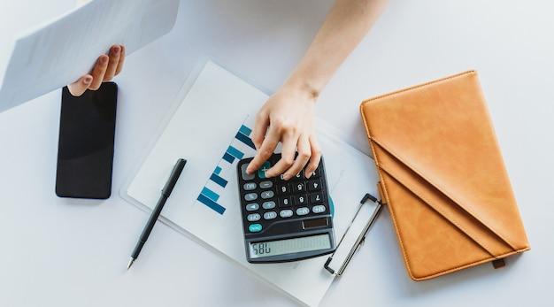 La giovane donna asiatica sta calcolando la tassa da pagare