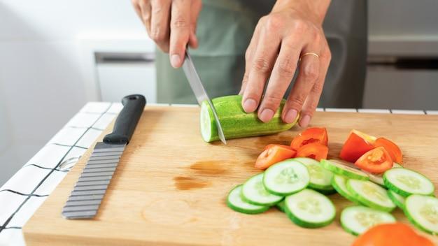 Giovane donna asiatica sta preparando insalata di verdure cibo sano tagliando gli ingredienti sul tagliere