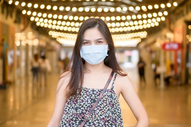 Una giovane donna asiatica indossa maschera protettiva shopping nel centro commerciale, protezione coronavirus, nuovo concetto di stile di vita normale