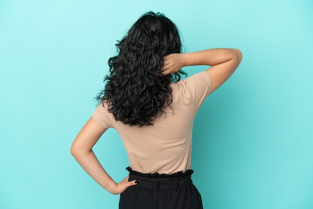 Giovane donna asiatica isolata su sfondo blu in posizione posteriore e pensando