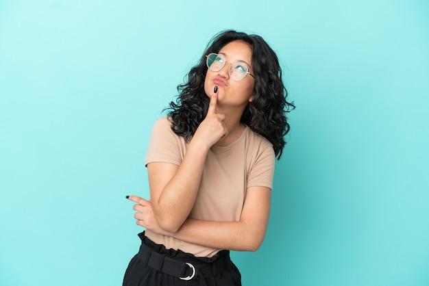 Giovane donna asiatica isolata su sfondo blu che ha dubbi mentre guarda in alto