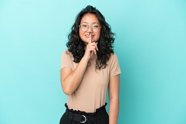 Giovane donna asiatica isolata su sfondo blu che mostra un segno di gesto di silenzio mettendo il dito in bocca