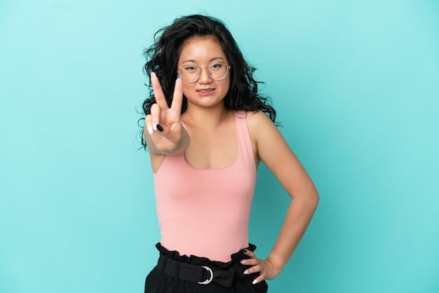 Giovane donna asiatica isolata su fondo blu che sorride e che mostra il segno di vittoria