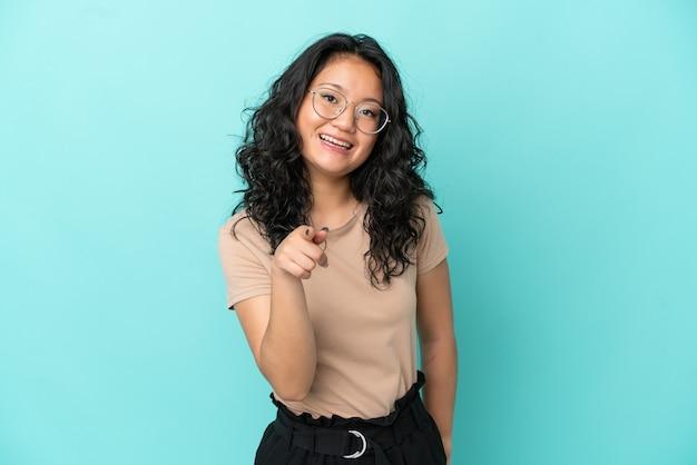 La giovane donna asiatica isolata su fondo blu ha sorpreso e che indica front