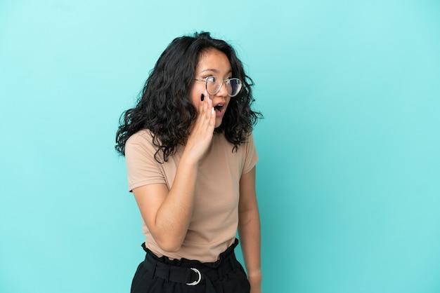 Giovane donna asiatica isolata su sfondo blu che sussurra qualcosa con un gesto di sorpresa mentre guarda di lato