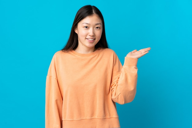 Giovane donna asiatica sopra la parete isolata