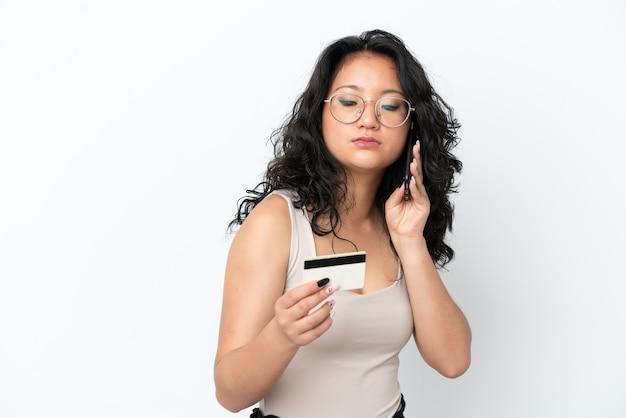 Giovane donna asiatica isolata su sfondo bianco che acquista con il cellulare con una carta di credito