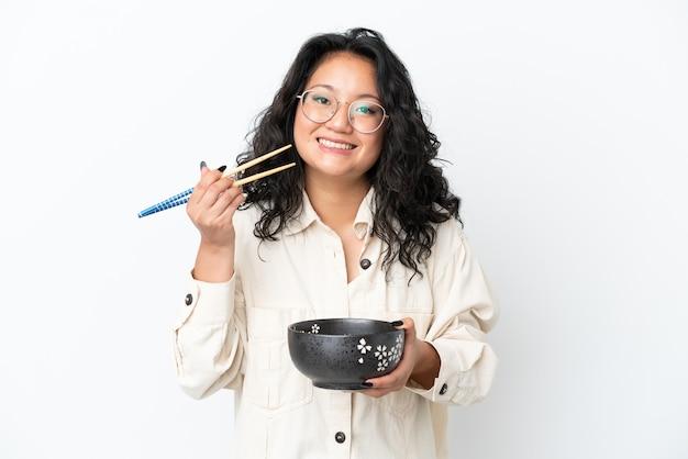 Giovane donna asiatica isolata su fondo bianco che tiene una ciotola di tagliatelle con i bastoncini