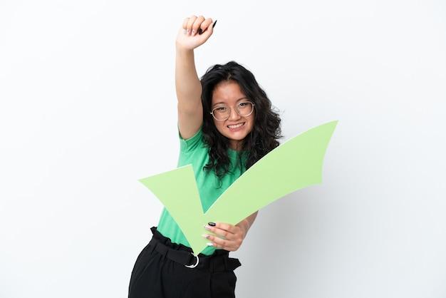 Giovane donna asiatica isolata su sfondo bianco con in mano un'icona di spunta e celebrando una vittoria