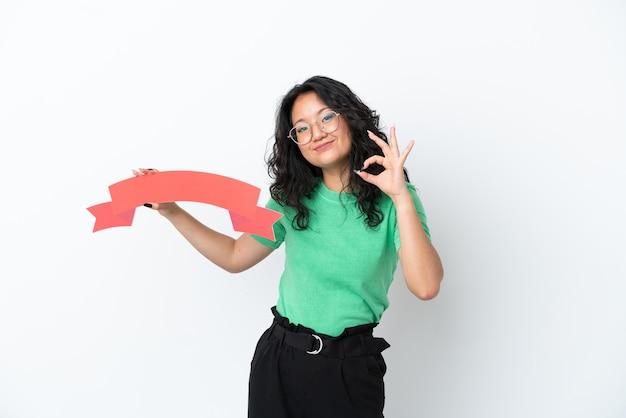 Giovane donna asiatica isolata su sfondo bianco con in mano un cartello vuoto e facendo segno ok
