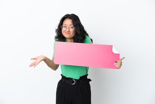 Giovane donna asiatica isolata su fondo bianco che tiene un cartello vuoto e che ha dubbi