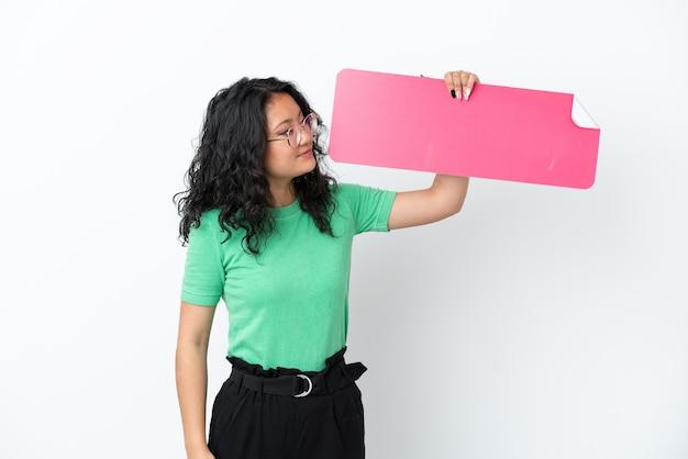 Giovane donna asiatica isolata su fondo bianco che tiene un cartello vuoto