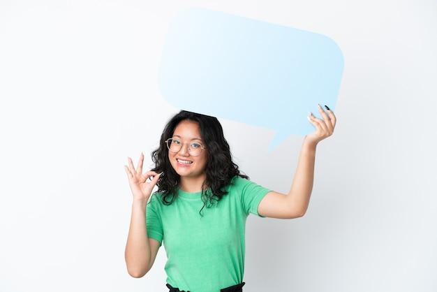 Giovane donna asiatica isolata su sfondo bianco in possesso di un fumetto vuoto e facendo segno ok