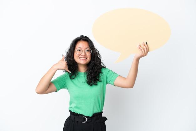 Giovane donna asiatica isolata su fondo bianco che tiene un fumetto vuoto e fa il gesto del telefono