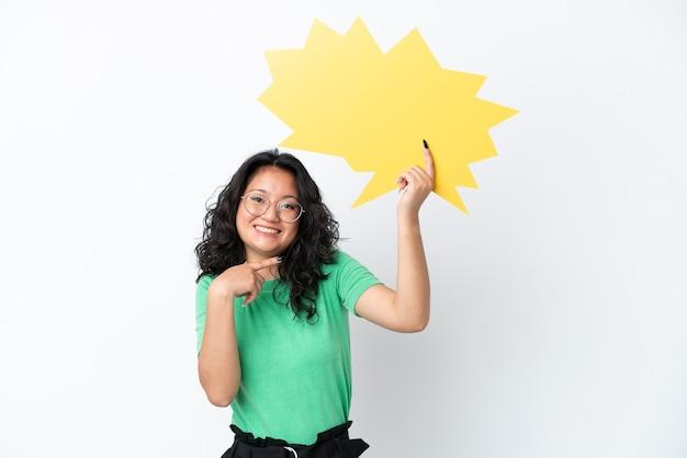 Giovane donna asiatica isolata su fondo bianco che tiene un fumetto vuoto e lo indica