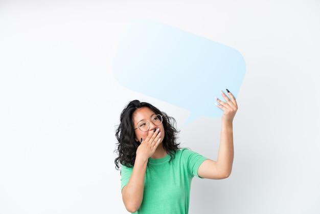 Giovane donna asiatica isolata su fondo bianco che tiene un fumetto vuoto con espressione sorpresa