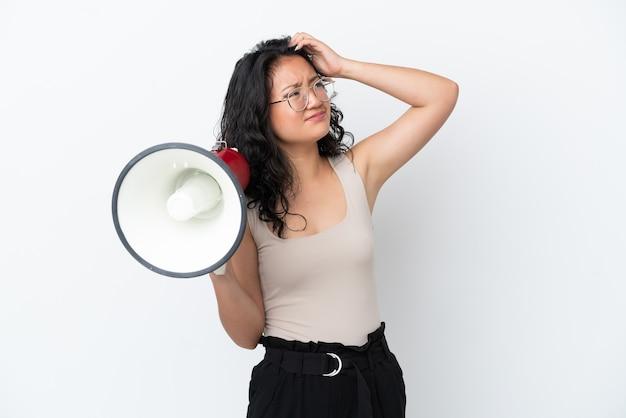 Giovane donna asiatica isolata su fondo bianco che tiene un megafono e che ha dubbi