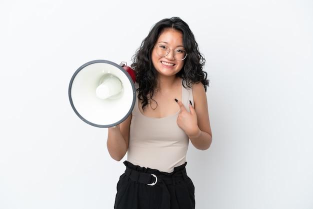 Giovane donna asiatica isolata su fondo bianco che tiene un megafono e con l'espressione facciale di sorpresa