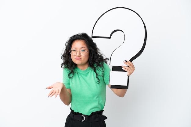 Giovane donna asiatica isolata su fondo bianco che tiene un'icona del punto interrogativo e che ha dubbi