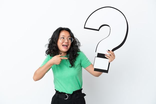 Giovane donna asiatica isolata su fondo bianco che tiene un'icona del punto interrogativo con l'espressione sorpresa