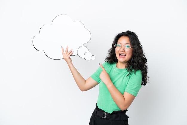 Giovane donna asiatica isolata su fondo bianco che tiene un fumetto di pensiero con espressione sorpresa