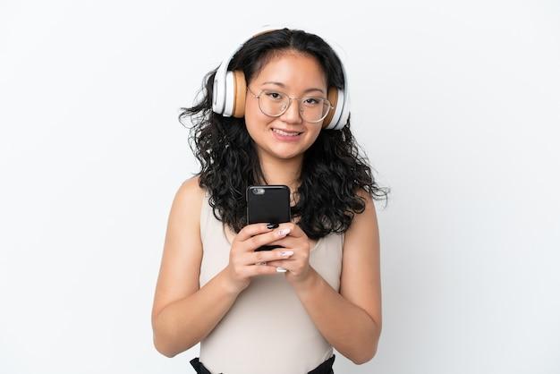 Giovane donna asiatica isolata su sfondo bianco ascoltando musica con un cellulare e guardando davanti