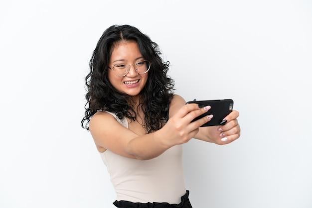 Giovane donna asiatica isolata su sfondo bianco che gioca con il cellulare