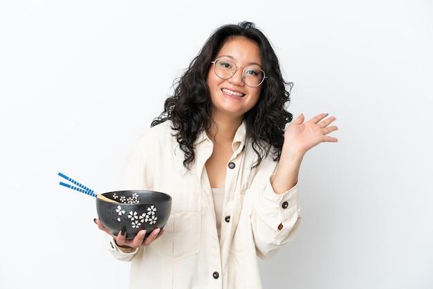 Giovane donna asiatica isolata su fondo bianco che saluta con la mano con l'espressione felice mentre tiene una ciotola di tagliatelle con i bastoncini