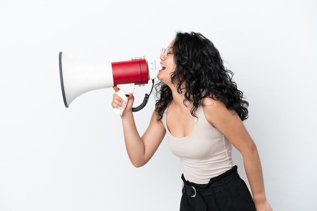 Giovane donna asiatica isolata su sfondo bianco che grida attraverso un megafono per annunciare qualcosa in posizione laterale